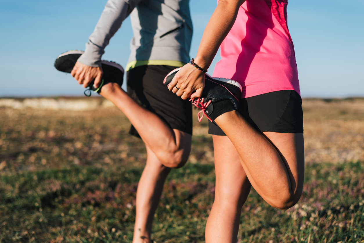 Man and woman stretching legs on run to see if working out helps spider veins