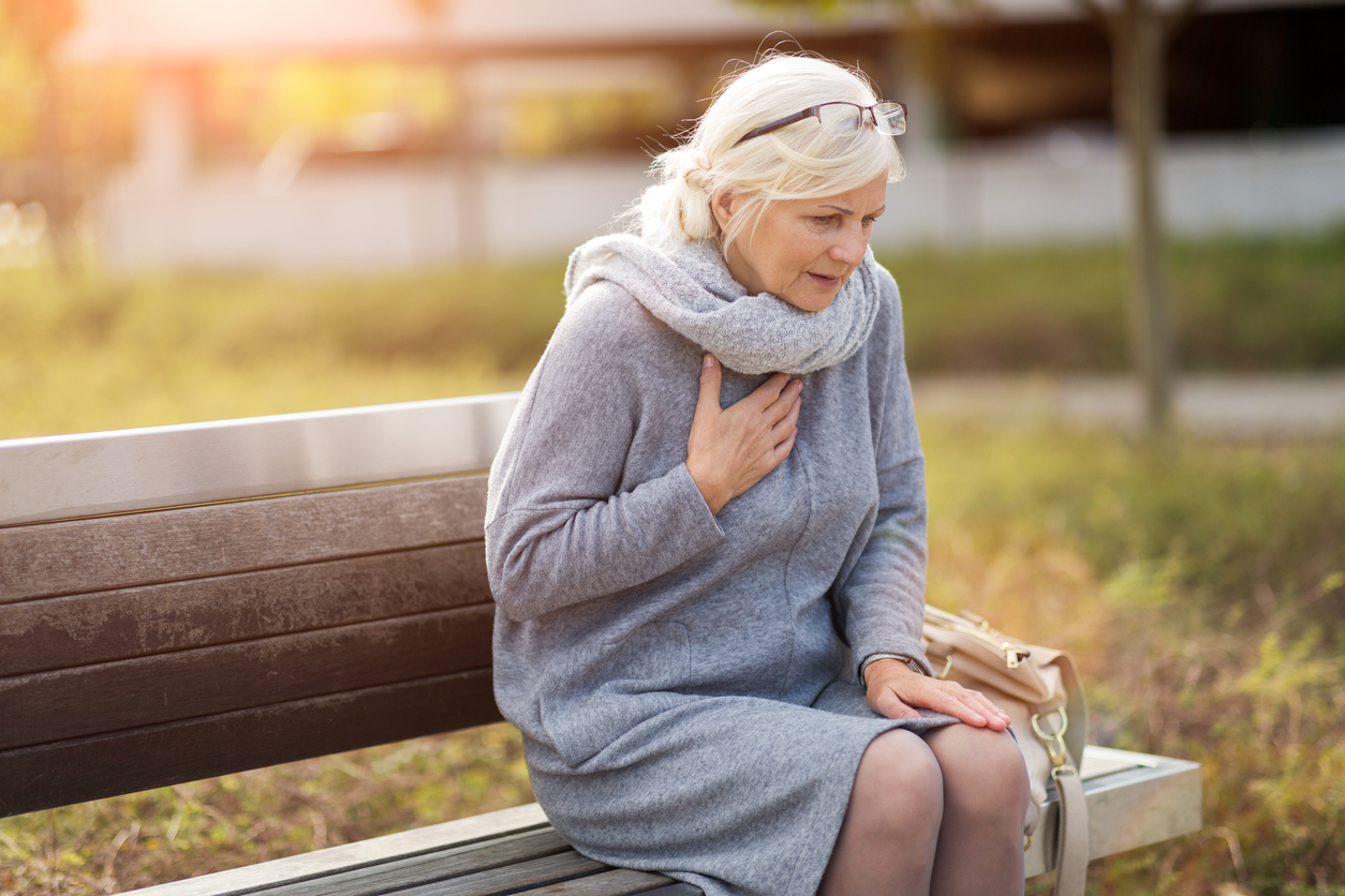 Woman on bench experiencing signs of a heart attack